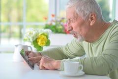 Schöner alter Mann, der eine Zeitung liest Lizenzfreie Stockfotografie