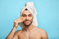 Schöner angenehmer Mann, der Gesicht mit kosmetischem Schwamm abwischt stockbilder