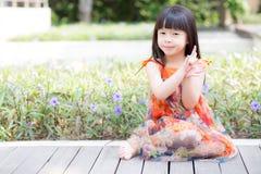 Schöner Asiat des kleinen Mädchens des Porträts einer lächelnden Stellung auf grünem Gras am Park Stockfoto