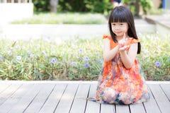 Schöner Asiat des kleinen Mädchens des Porträts einer lächelnden Stellung auf grünem Gras am Park Lizenzfreie Stockfotografie