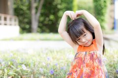 Schöner Asiat des kleinen Mädchens des Porträts einer lächelnden Stellung auf grünem Gras am Park Stockbilder