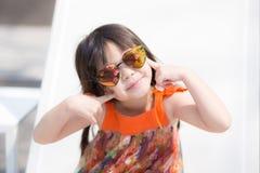 Schöner Asiat des kleinen Mädchens des Porträts eines lächelnden Sitzens am Swimmingpool Lizenzfreies Stockfoto