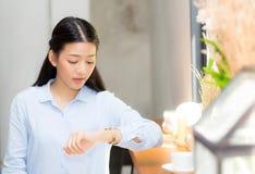 Schöner asiatischer Blick der jungen Frau auf Uhrwartefreund oder -jemand stockfotografie