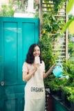 Schöner asiatischer Frauengärtner, der die Anlagen, achtern entspannend wässert Stockfotografie