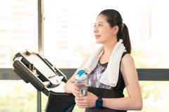 Schöner asiatischer Frauenrest, der Wasserflasche nach Tretmühle hält Lizenzfreie Stockfotos