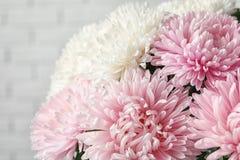 Schöner Asterblumenblumenstrauß nahe Backsteinmauer stockfoto