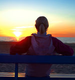 Schöner Athlet auf dem überwachenden Sonnenuntergang des Strandes Lizenzfreie Stockfotografie