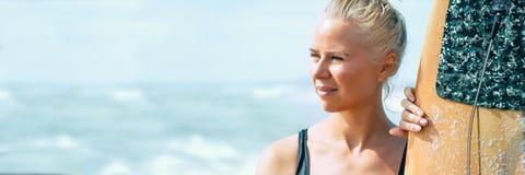 Schöner Athletenmädchensurfer mit einem Brett bei Sonnenaufgang Sommerferien in Meer, gesunder Lebensstil fahne stockfoto