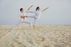 Schöner athletischer Paartrainingstanz auf dem Strand Lizenzfreie Stockbilder
