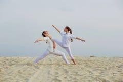 Schöner athletischer Paartrainingstanz auf dem Strand Stockbilder