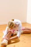 Schöner Balletttänzer, der unten auf Fahrwerkbeinen sich lehnt Lizenzfreies Stockbild