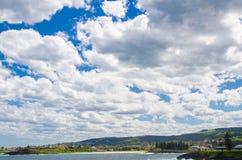 Schöner bewölkter Himmel über grünem Stadthügel von Kiama, New South Wales, Australien stockfotos