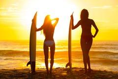 Schöner Bikini-Surfer-Frauen-Mädchen-Surfbrett-Sonnenuntergang-Strand stockbilder