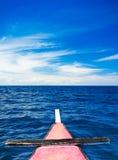 Schöner blauer Himmel, der auf einem Boot sitzt Lizenzfreie Stockbilder
