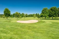 Schöner blauer Himmel des Golfplatzlandschaftsgrünfeldes stockfotografie