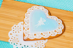 Schöner blauer Pastelllebkuchen mit Bild eines netten kleines Mädchen Elfe und Tracery Doily, hölzerne Planken des Hintergrundes Stockbild