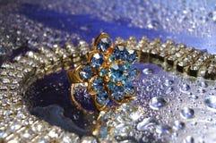 Schöner blauer Ring mit Halskette auf silbernem Hintergrund mit Tropfen Stockbild