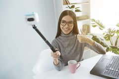 Schöner Blogger sitzt am Tisch im hellen Raum und nimmt selfie unter Verwendung eines Selfiestockes für das Sie schaut Stockfotos
