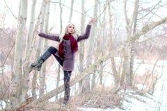 Schöner blonder Aufenthalt nahe Bäumen, Hand oben, führte, beleuchtet backgro Stockfoto