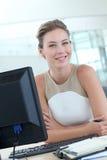 Schöner blonder Büroangestellter auf Tischrechner Stockbild