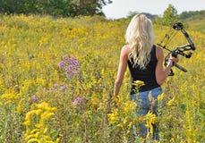 Schöner blonder Bogenschütze auf dem Gebiet von Wildflowers stockfotos
