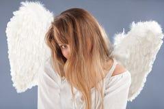 Schöner blonder Engel gegen grauen Hintergrund Stockfotos