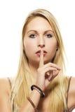 Schöner blonder Frauenholdingfinger an ihrem Mund Lizenzfreies Stockbild
