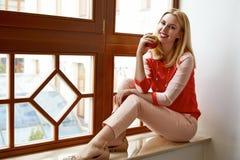 Schöner blonder Frauensitz nahe Fensterlächeln-Grünapfel Lizenzfreies Stockfoto