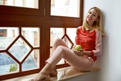 Schöner blonder Frauensitz nahe Fensterlächeln-Grünapfel Stockfotos