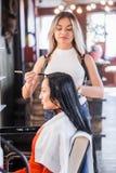 Schöner blonder Friseur macht den Badekurort auf langer Haar Brunettefrau Lizenzfreie Stockfotos