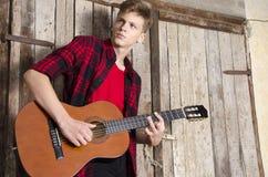 Schöner blonder Jugendlicher, der klassische Gitarre spielt Lizenzfreies Stockbild