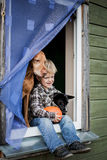 Schöner blonder Junge, der auf Fensterbrett mit zwei Hunden und Griffkürbis sitzt Stockbild