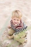 Schöner blonder Junge, der mit Sand auf dem Strand spielt Stockfotos