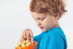 Schöner blonder Junge, der Popcorn isst Stockfotos