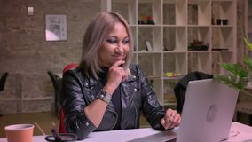 Schöner blonder kaukasischer der Frau Blick stolz auf den Schirm des Laptops und des Schreibens auf Tastatur beim Sitzen Innen stock video footage