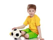 Schöner blonder kleiner Junge in einem gelben Hemd Lizenzfreie Stockfotografie