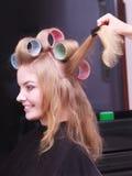 Schöner blonder Mädchenhaarlockenwickler-Rollenfriseur-Schönheitssalon Lizenzfreies Stockfoto
