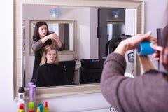 Schöner blonder Mädchenhaarlockenwickler-Rollenfriseur-Schönheitssalon Stockfotos