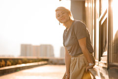 Schöner blonder Mädchenstand gegen Stadtansicht in sonnige Strahlen bei Sonnenuntergang im Sommer Stockfotos