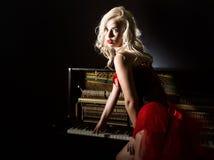 Schöner blonder Musiker im roten Korsett, das nahe dem Klavier steht Weinleseartschönheit Stockfotografie