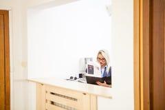 Schöner blonder Sekretär, der Ordner mit Dokumenten betrachtet Stockfoto