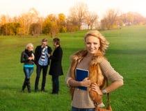 Schöner blonder Student mit Freunden Stockfoto