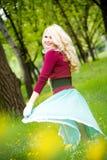 Schöner blonder tragender langer Rock im Sommerpark Stockfotos