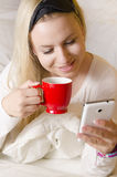 Schöner blonder trinkender Morgenkaffee und Prüfung des intelligenten Telefons Lizenzfreie Stockfotos