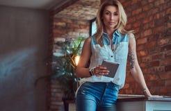 Schöner blonder weiblicher Blogger hält eine Tablette bei der Stellung auf einer Tabelle gegen eine Backsteinmauer in einem Studi Lizenzfreie Stockfotografie