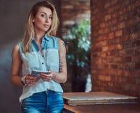 Schöner blonder weiblicher Blogger hält eine Tablette bei der Stellung auf einer Tabelle gegen eine Backsteinmauer in einem Studi Stockfotos