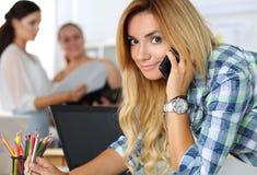 Schöner blonder weiblicher Designer in Unterhaltungsmobiltelefon des Büros Stockbilder