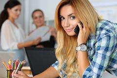 Schöner blonder weiblicher Designer in Unterhaltungsmobiltelefon des Büros Stockfotografie