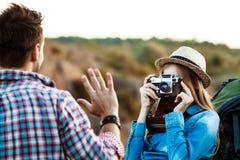 Schöner blonder weiblicher Fotograf, der Foto des Freundes, Schluchthintergrund macht Lizenzfreie Stockfotografie