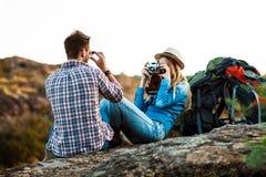 Schöner blonder weiblicher Fotograf, der Foto des Freundes, Schluchthintergrund macht Stockbild